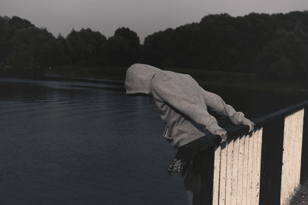 Man leaning over a bridge head facing down