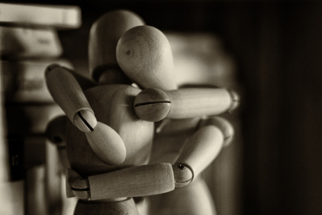 two wooden figures embracing