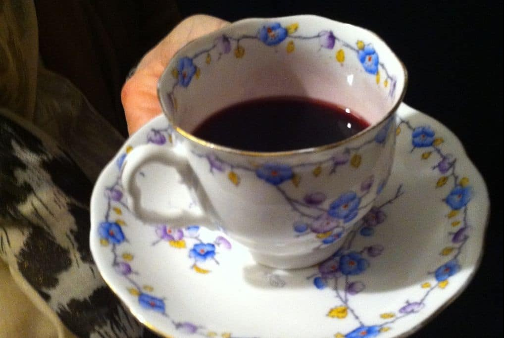 china tea cup filled with dark grape juice