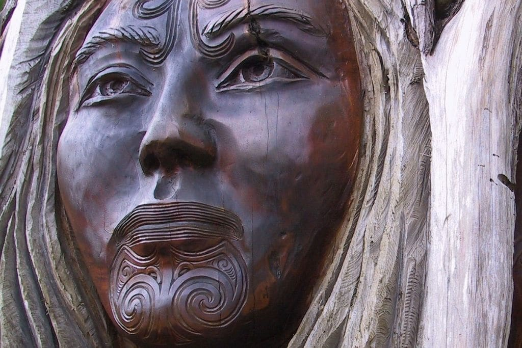 wooden carving of maori female face