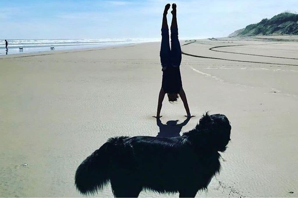 Julie doing a handstand on the beach with dog