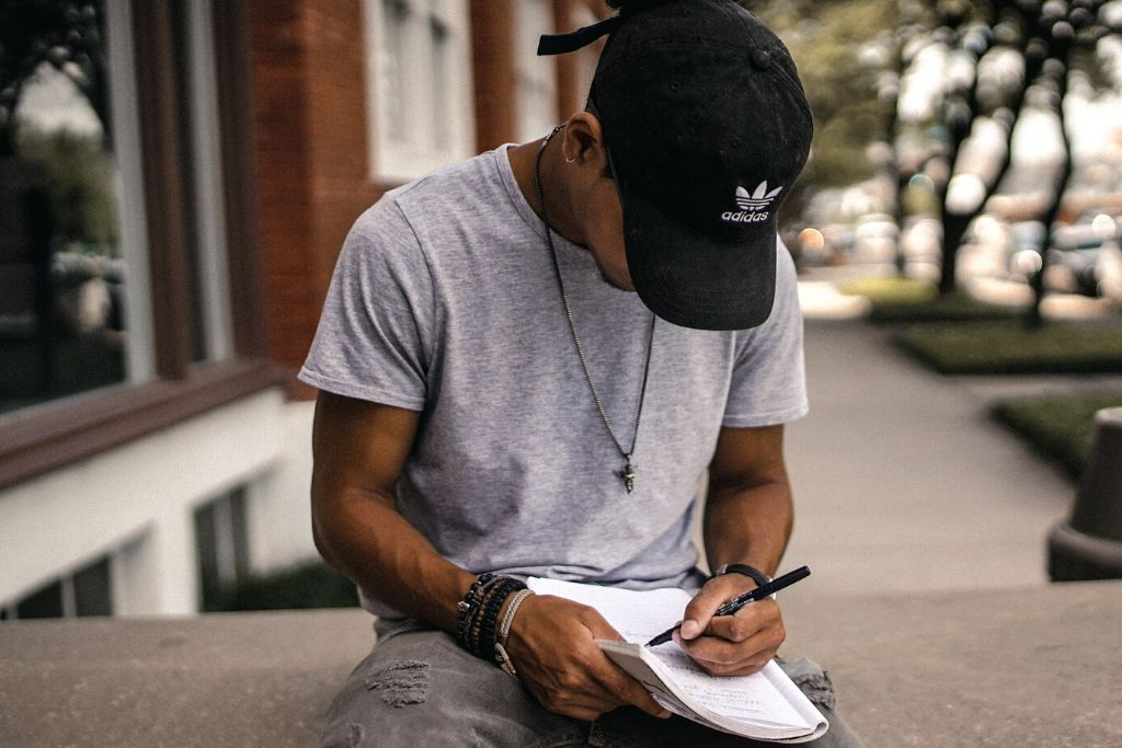 guy in cap writing in notebook